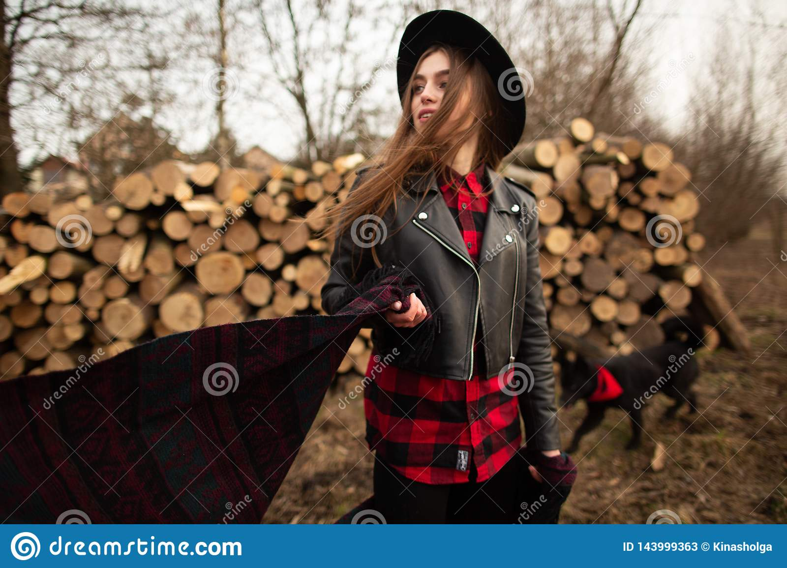 Girl in black hat posing against the background of a firewood and her dog