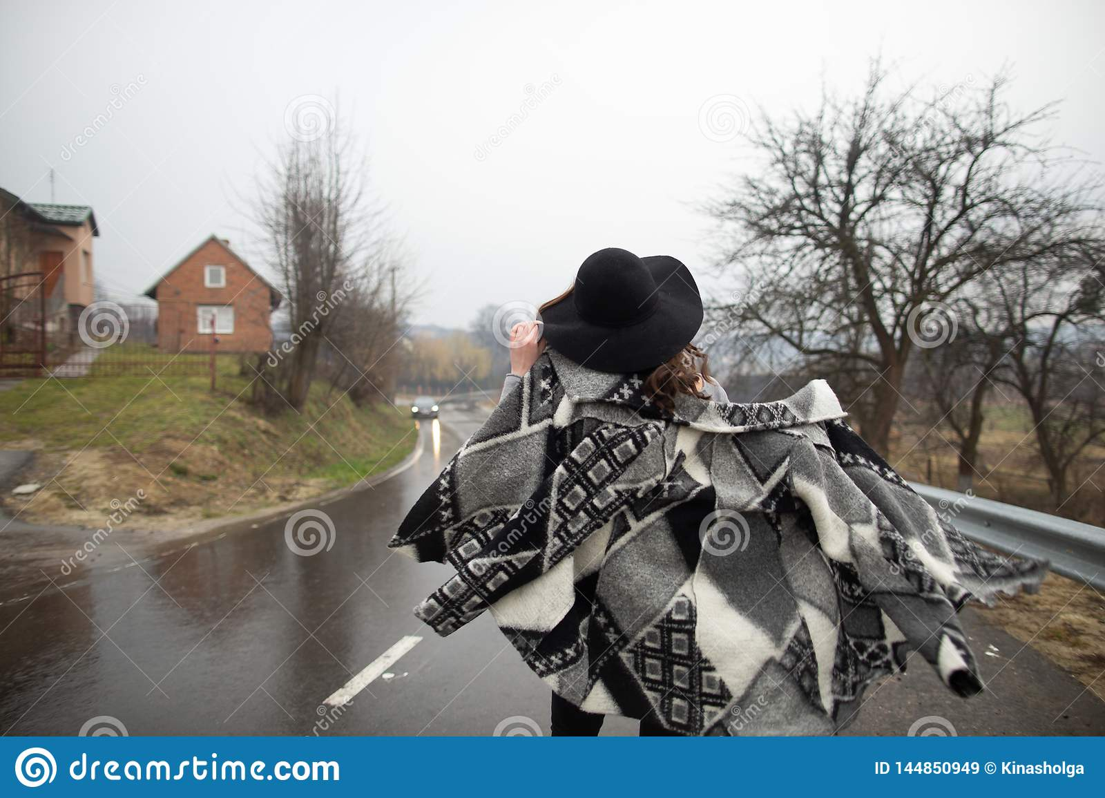 Girl with a black hat walking along the road on a rainy day