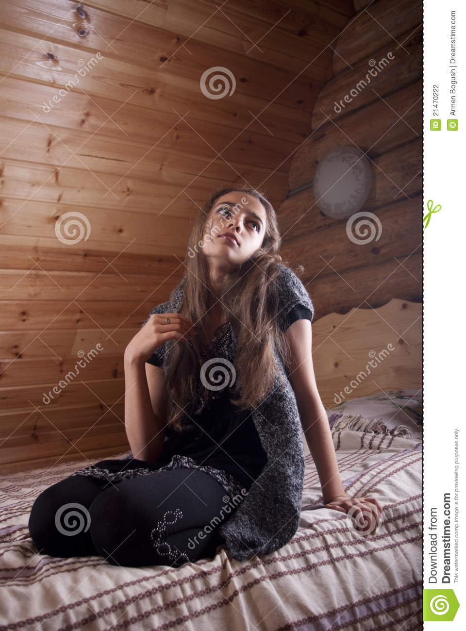 Girl In Black Jersey Sitting On Bed Stock Photo - Image