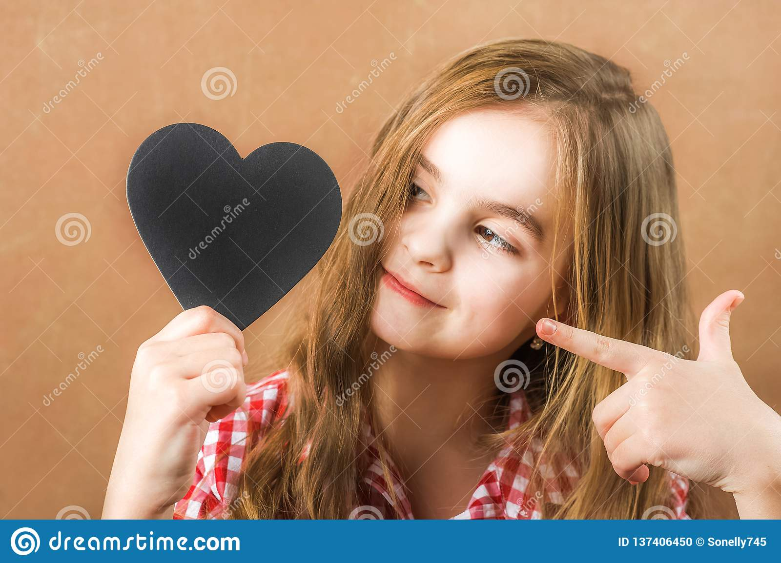 Girl and black slate heart. The girl builds a physiognomy, grimaces and a heart for an inscription. Valentine`s Day concept, close