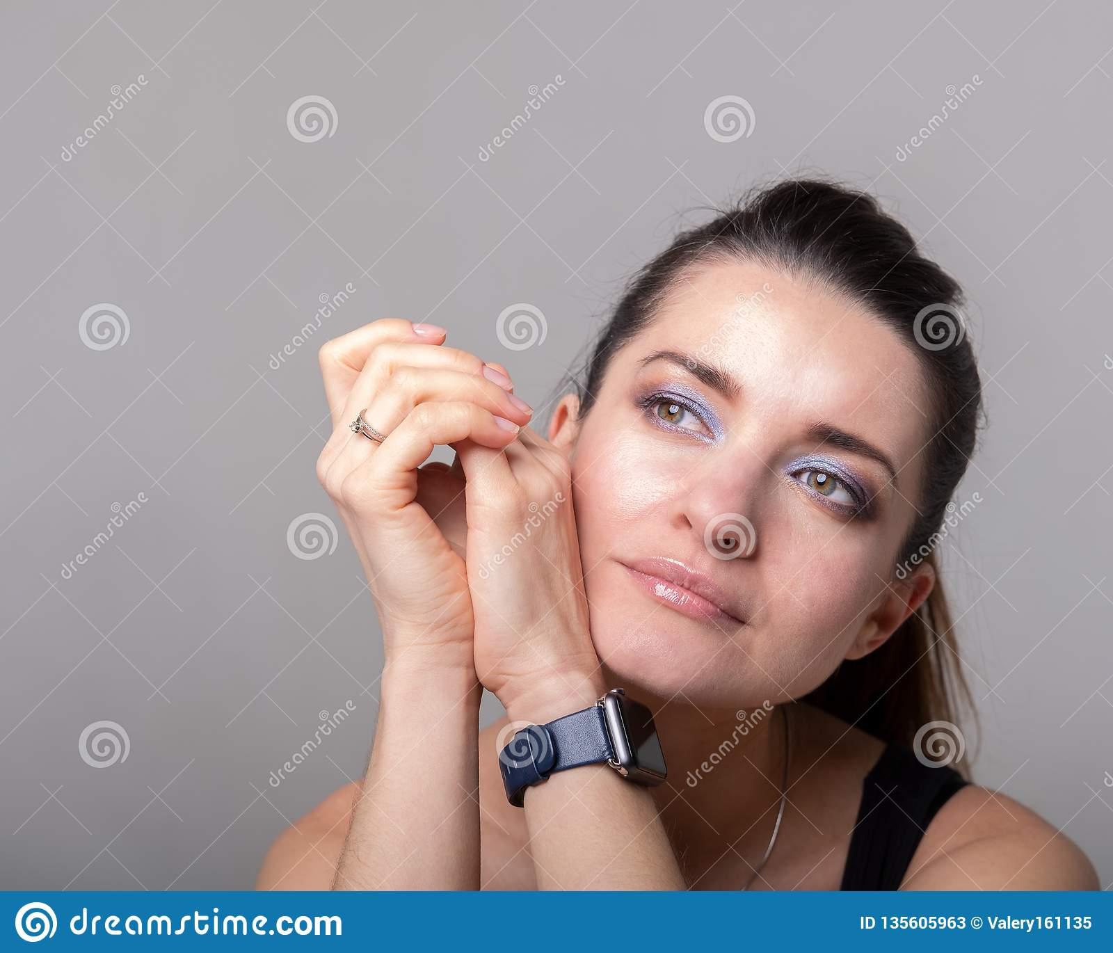 Girl in a black t-shirt holds her hands to her face