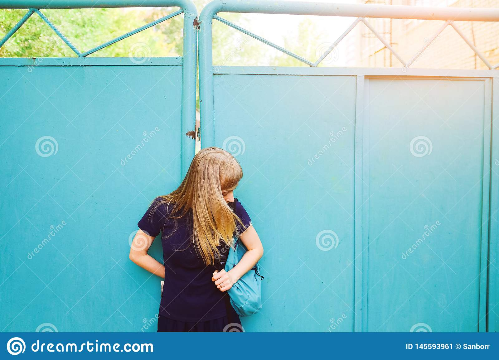 Girl with blond hair, blue Polo shirt, iron gate. The young woman looks down at her backpack. The concept of education