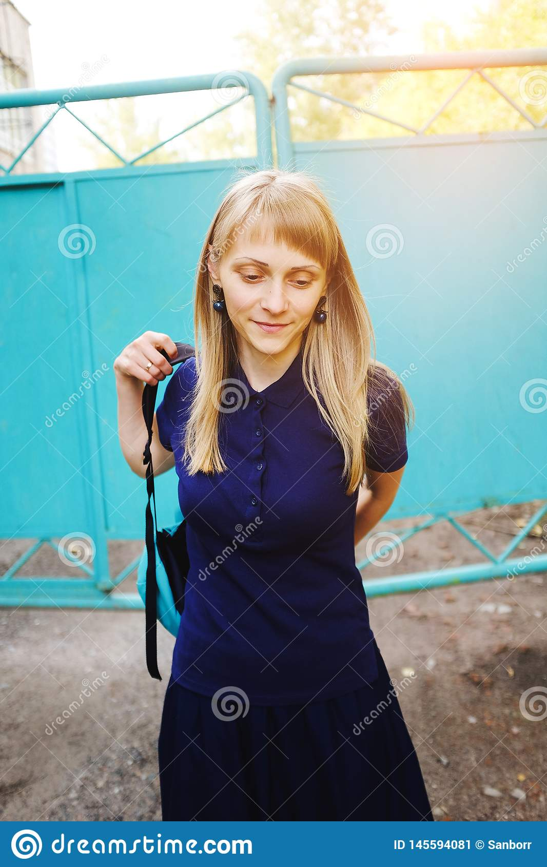 A girl with blond hair, wearing a blue Polo shirt. A young woman, looking down, puts on a backpack against the iron gate.