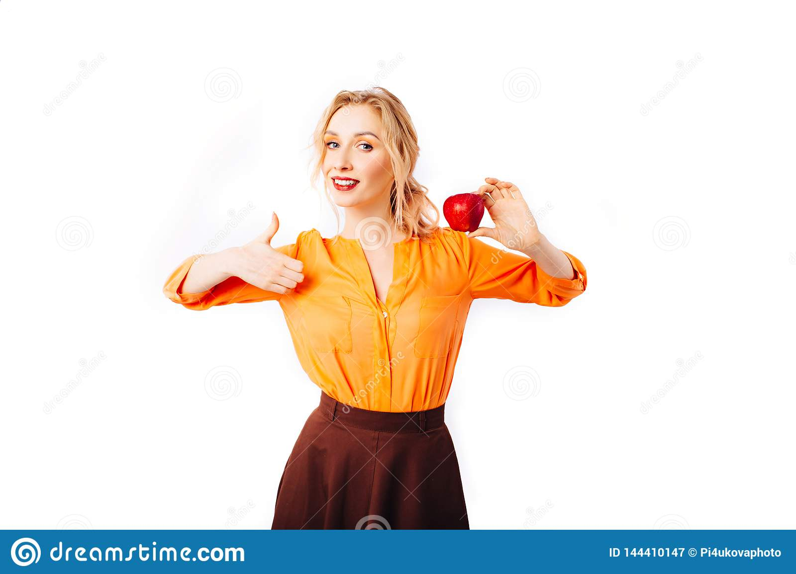Girl blonde in a bright orange sweater with an apple in her hands promotes healthy food.