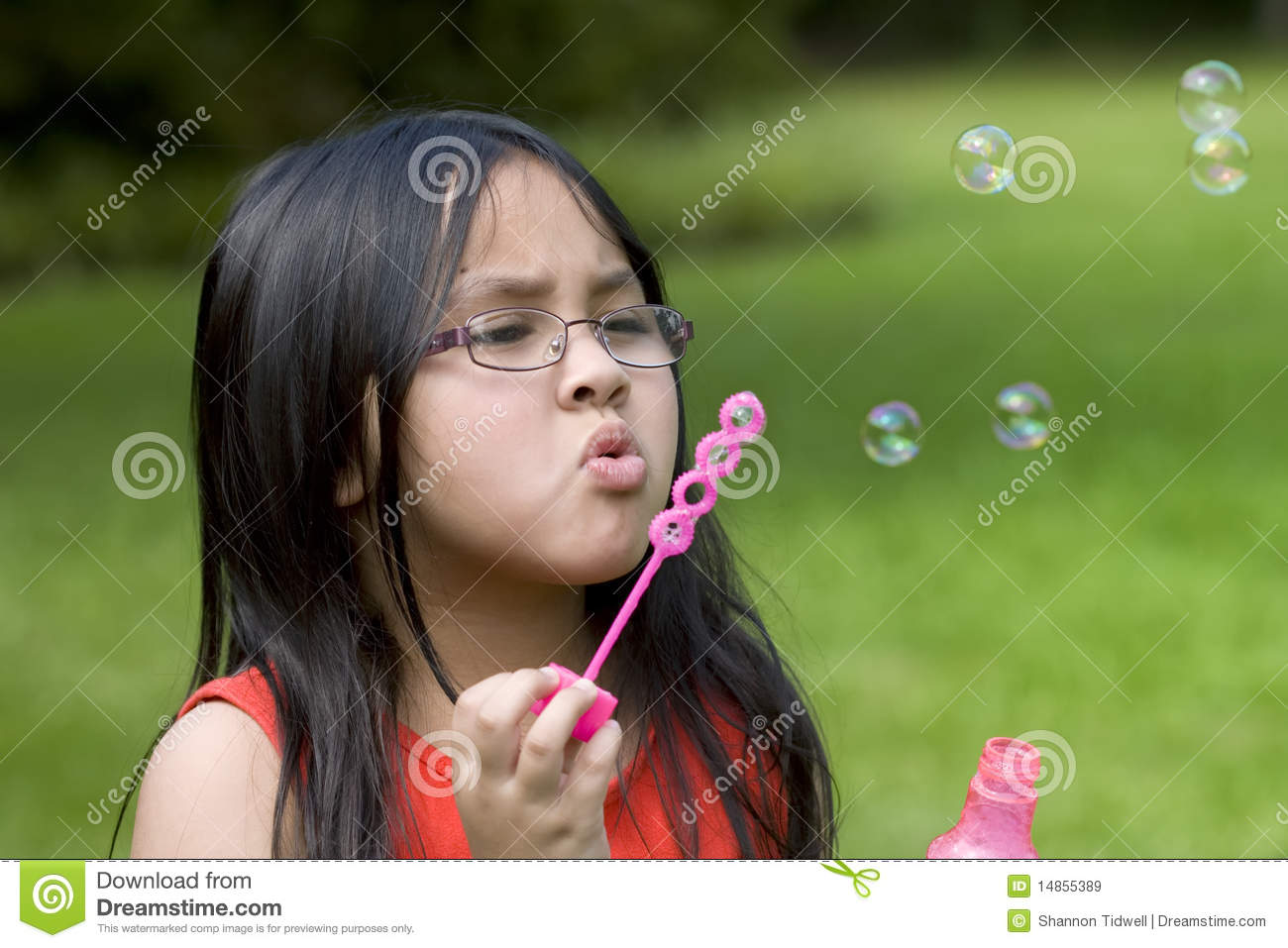 Girl blowing bubbles with wand