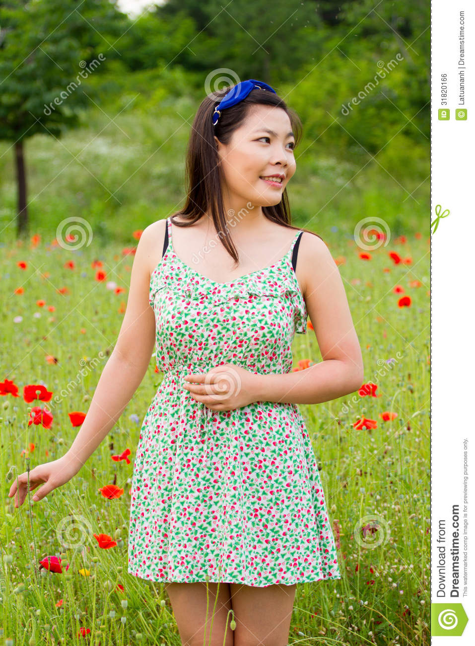 Girl with blue band stands in poppy field