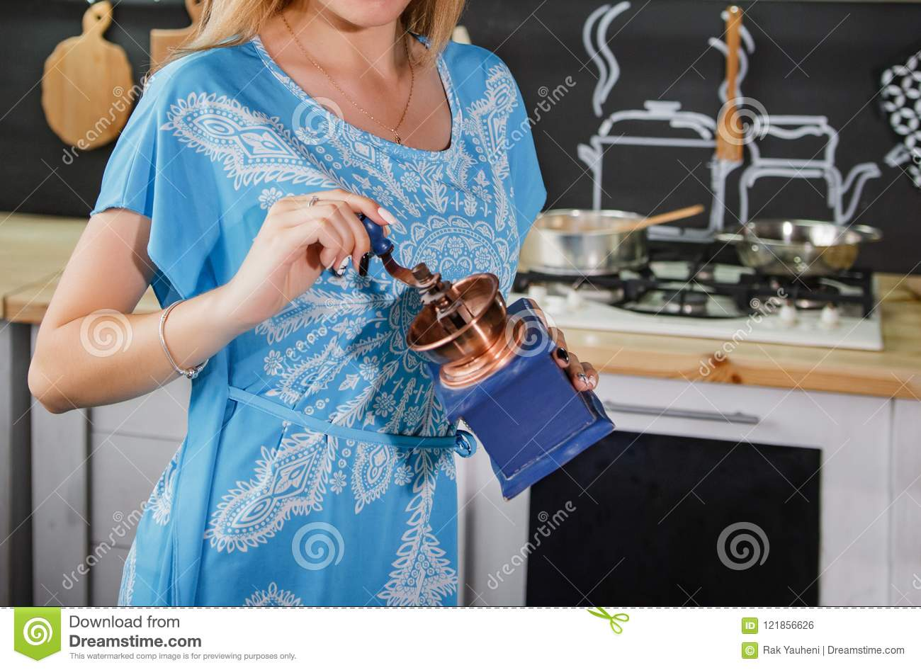 A girl in a blue dress grinds coffee. Girl with a coffee grinder
