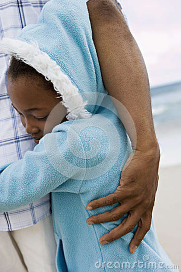 Girl (7-9) in blue fleece with hood embracing father on beach, smiling, eyes closed, close-up