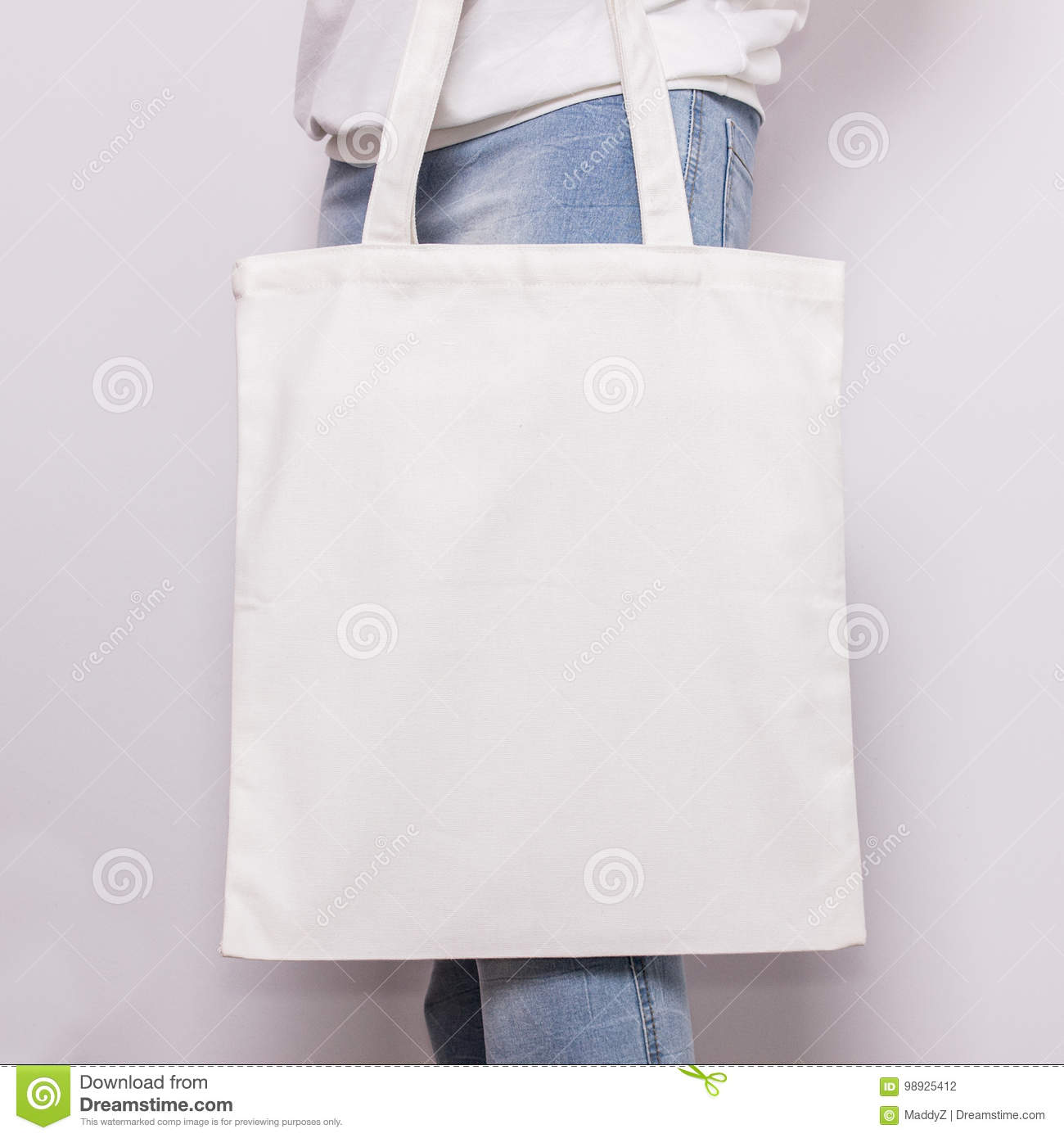 Girl in blue jeans holds blank cotton eco tote bag, design mockup. Handmade shopping bag for girls