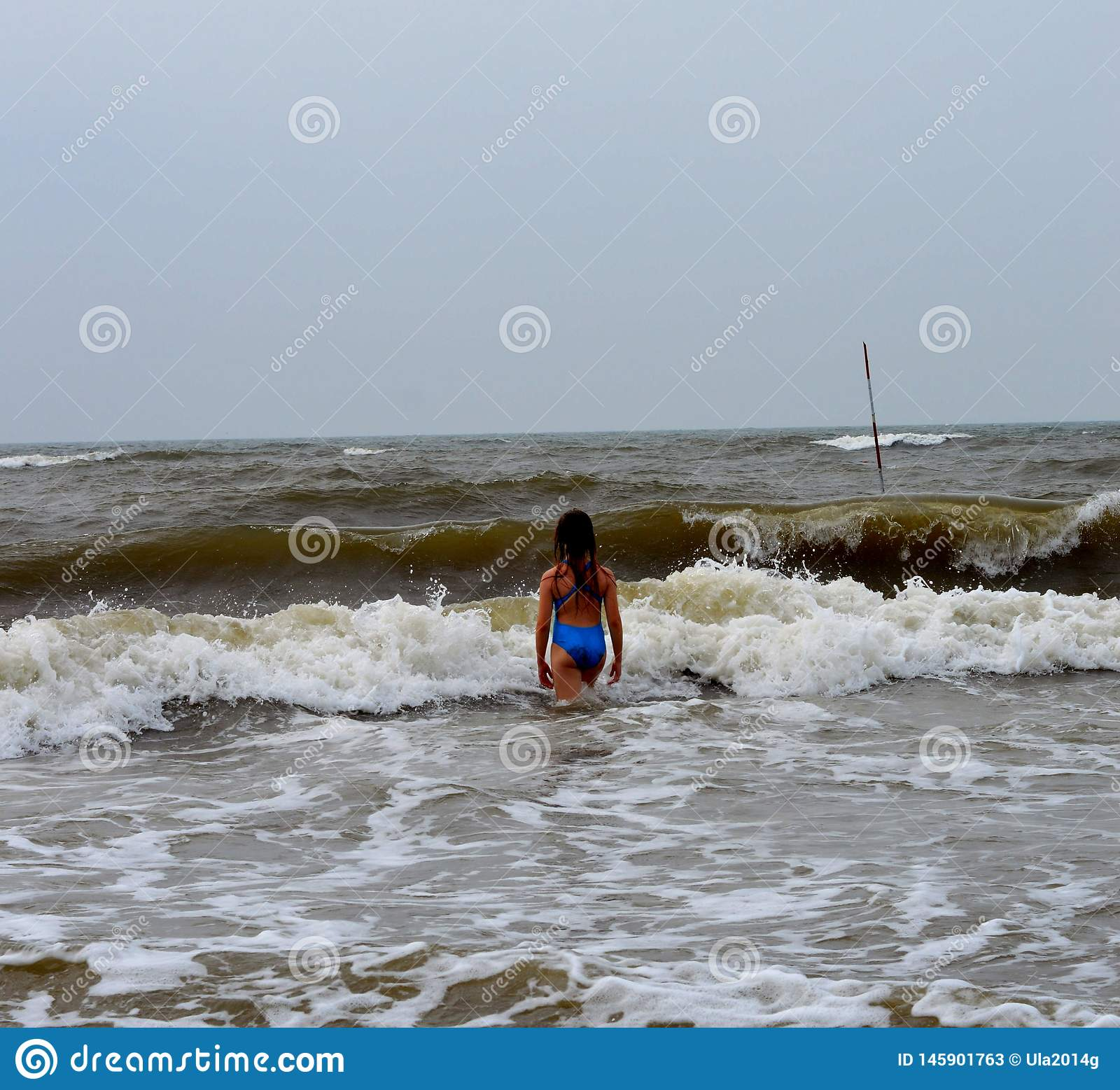 A girl in a blue swimsuit on the yellow sea