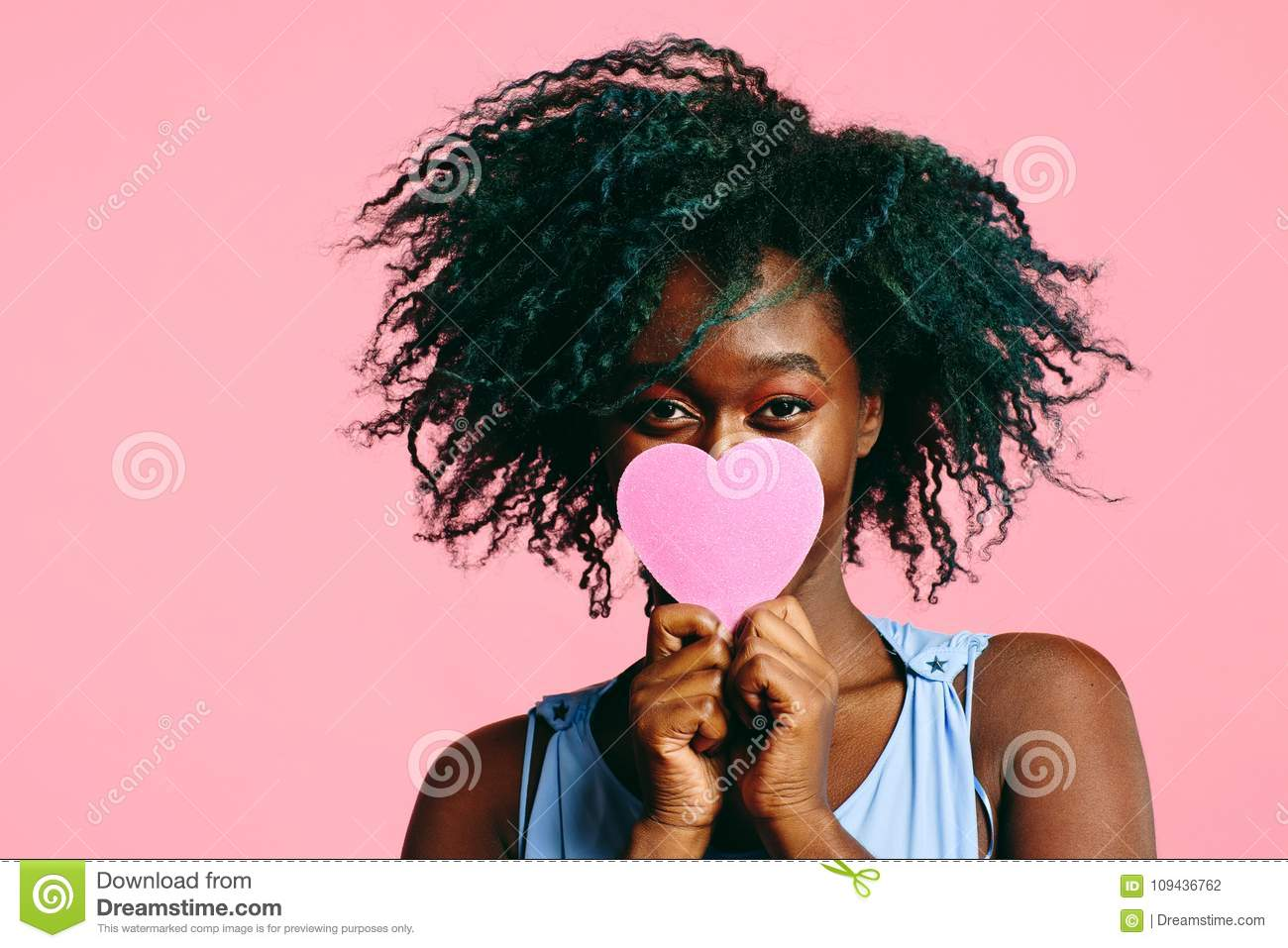 Girl with blueish black curly hair holding a pink heart in front of her face