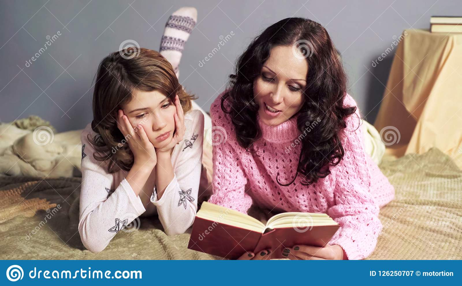 Girl bored with storybook her mother reading before bedtime, togetherness