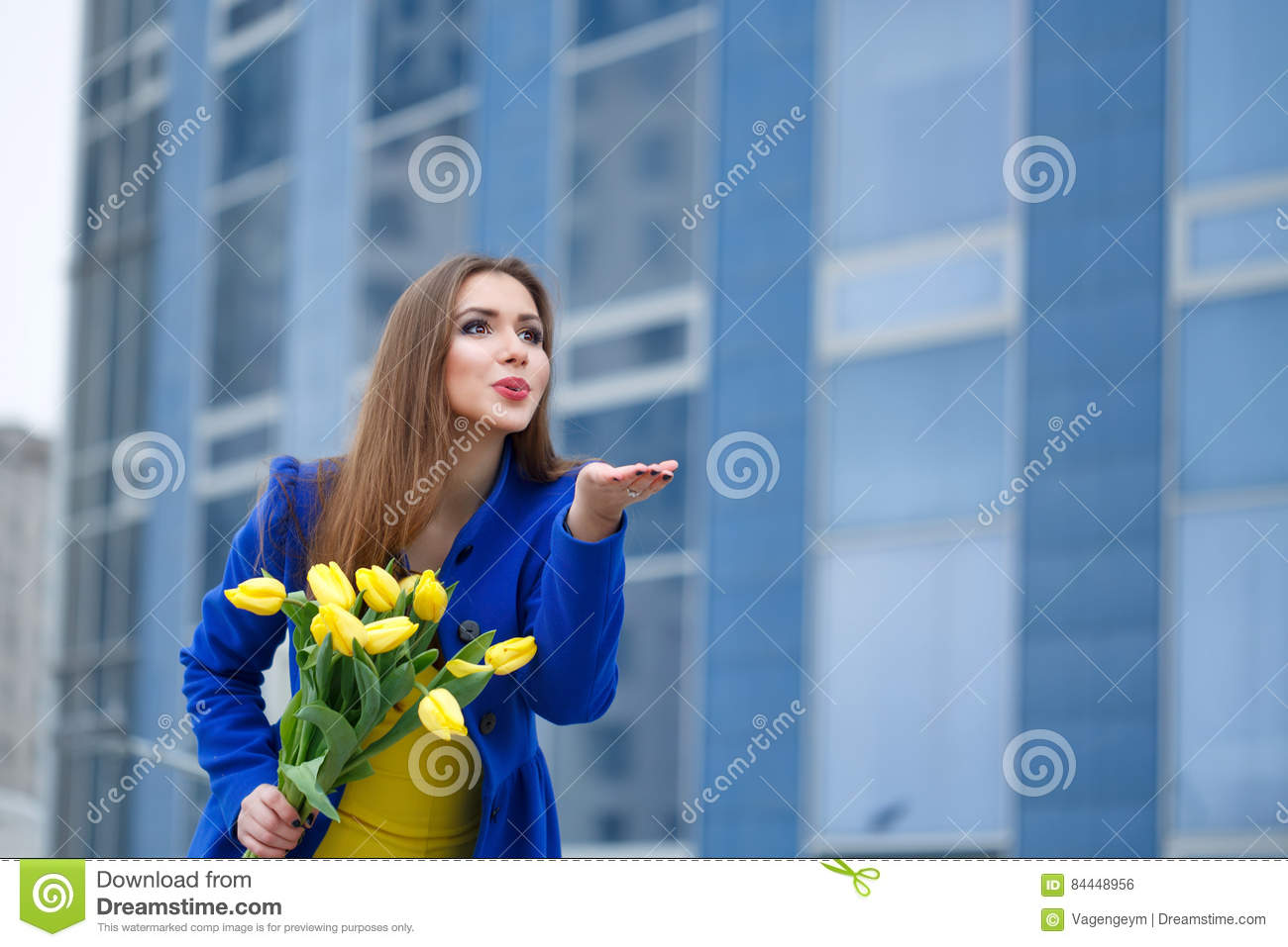 Young attractive girl in a blue coat and yellow dress holding a bouquet of  yellow tulips. Spring is coming to town. She sends a kiss to someone 66cb0a3c0