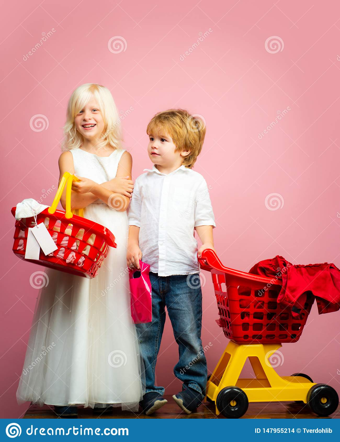 Girl and boy children shopping. Couple kids hold plastic shopping basket toy. Kids store. Mall shopping. Buy products