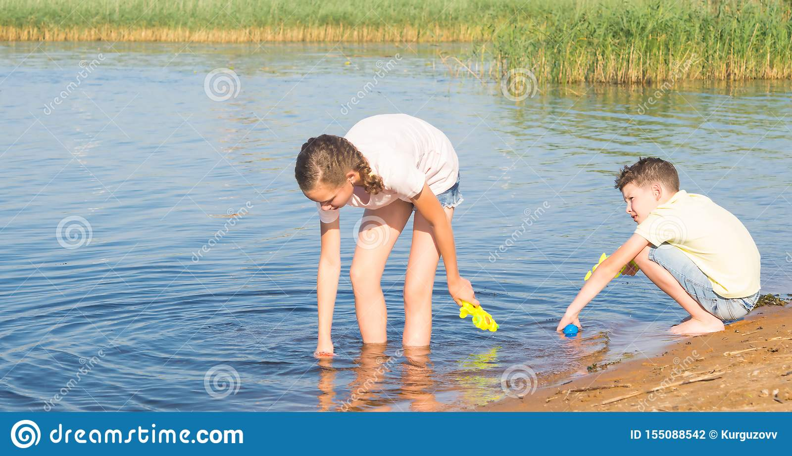 A girl and a boy collect water from a lake in water guns to play in them, against the backdrop of the landscape, close-up