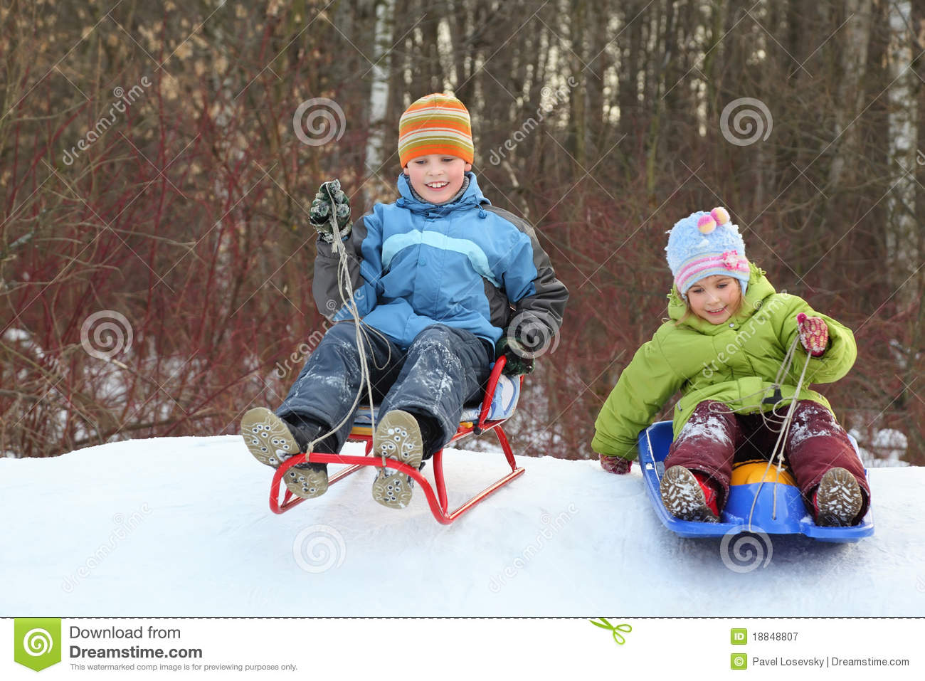 Girl and boy go downward from hill on sledges