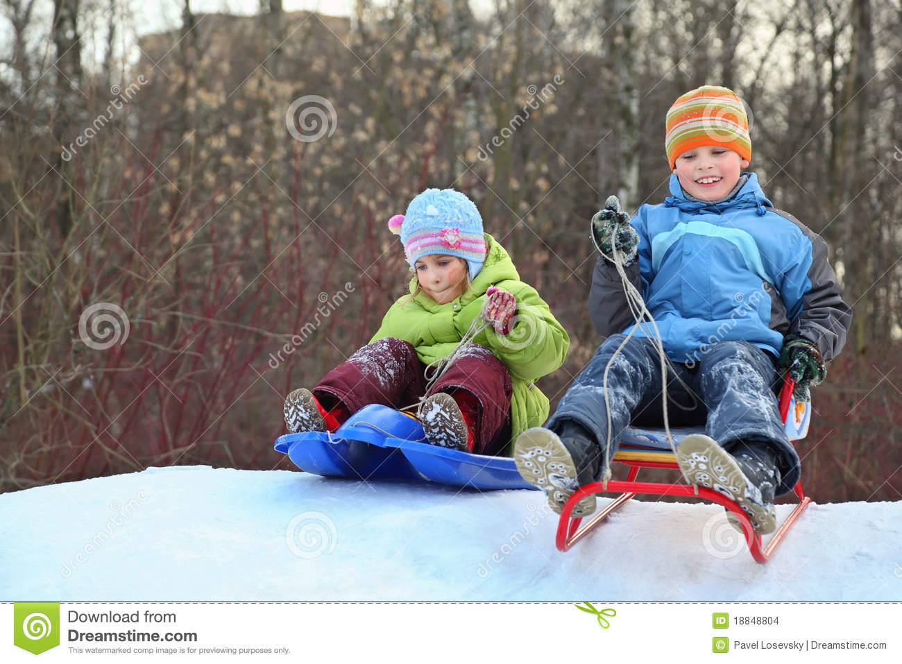 Girl and boy intend drive from hill on sledges