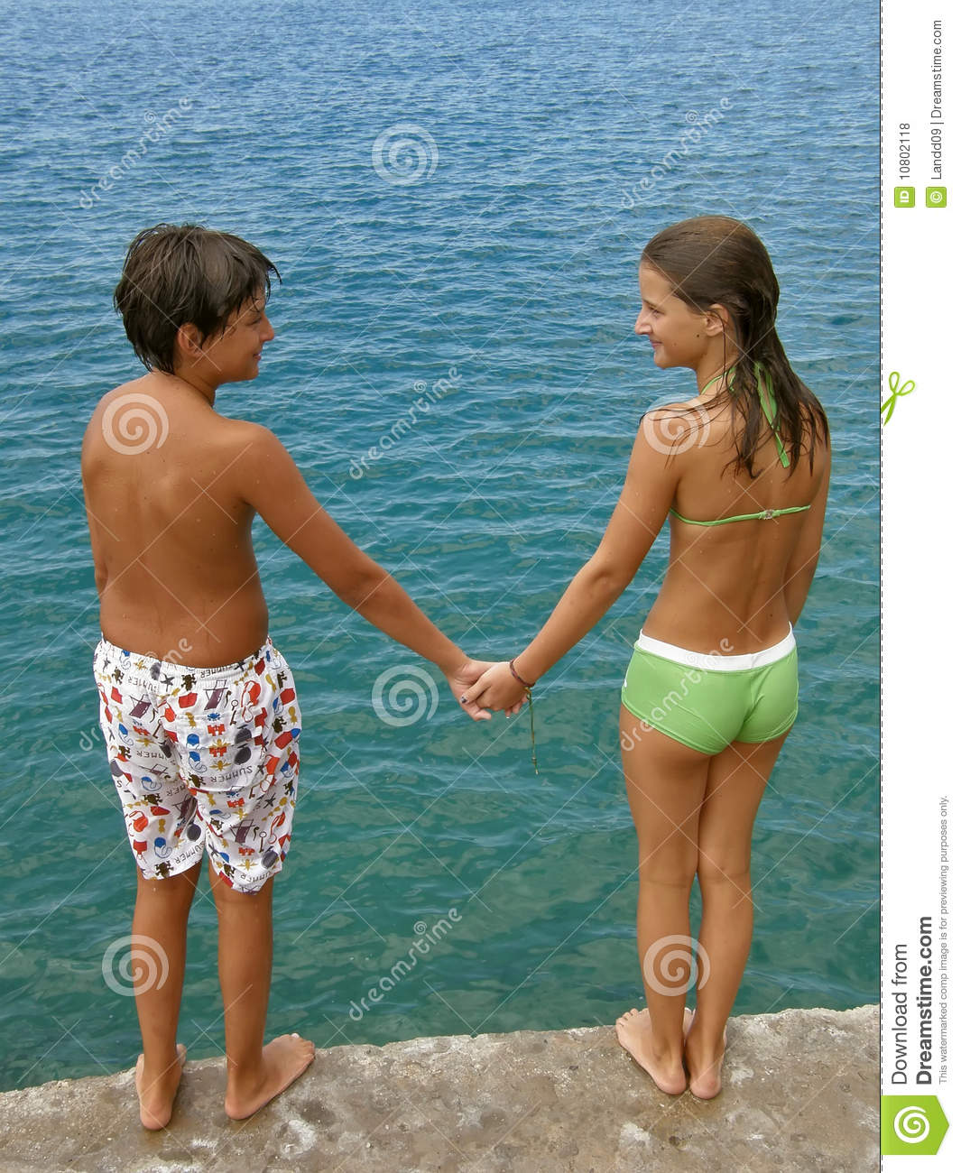 teenagers boy and girl hold hands lovingly looking facing each