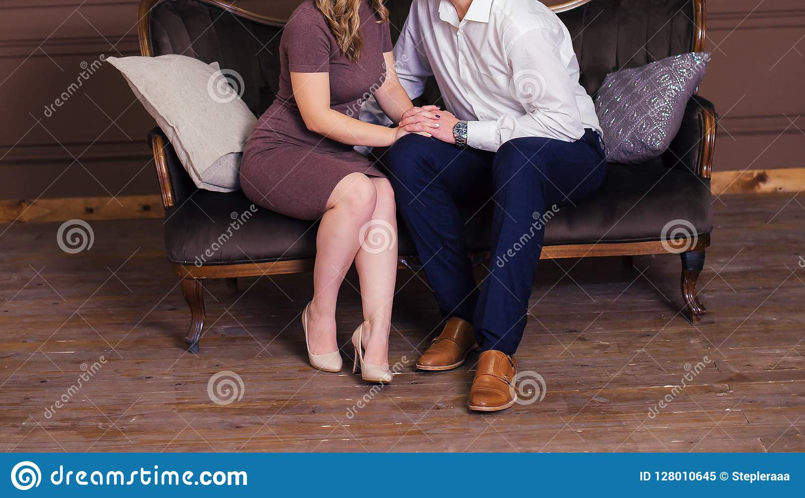 The girl and the boy in love are sitting on a luxurious couch in