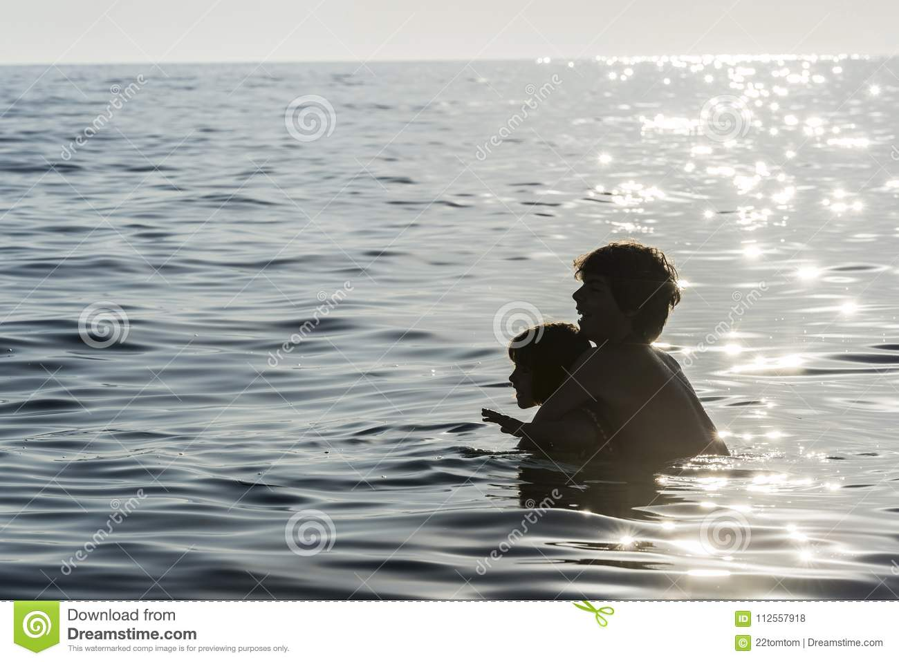 Girl and boy playing in the sea in summer
