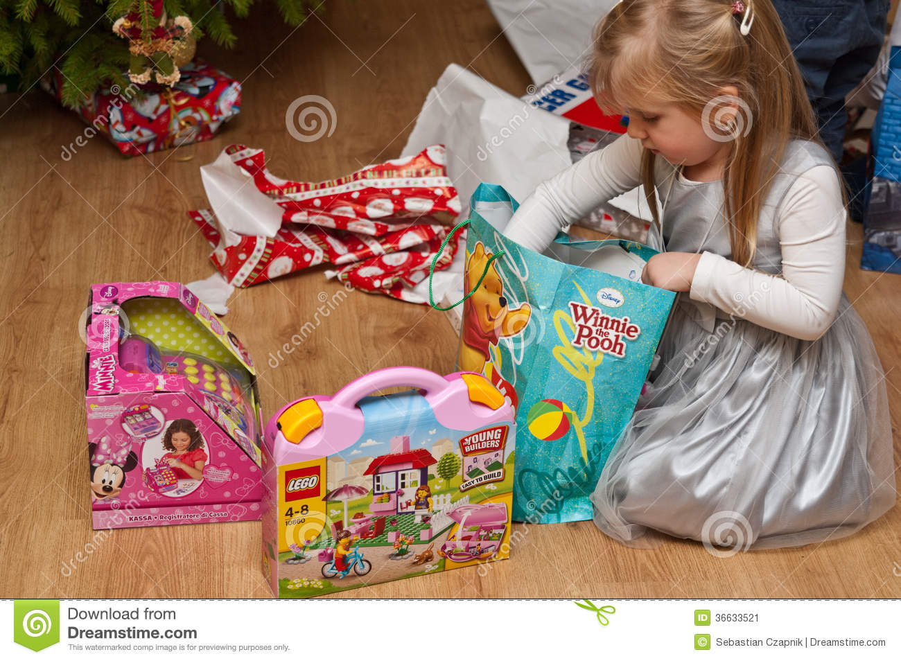 Toys Under Christmas Tree : Girl with branded toys under christmas tree editorial