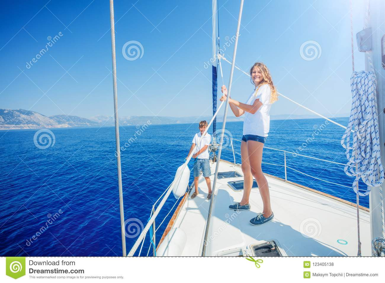 Girl with brother on board of sailing yacht on summer cruise.