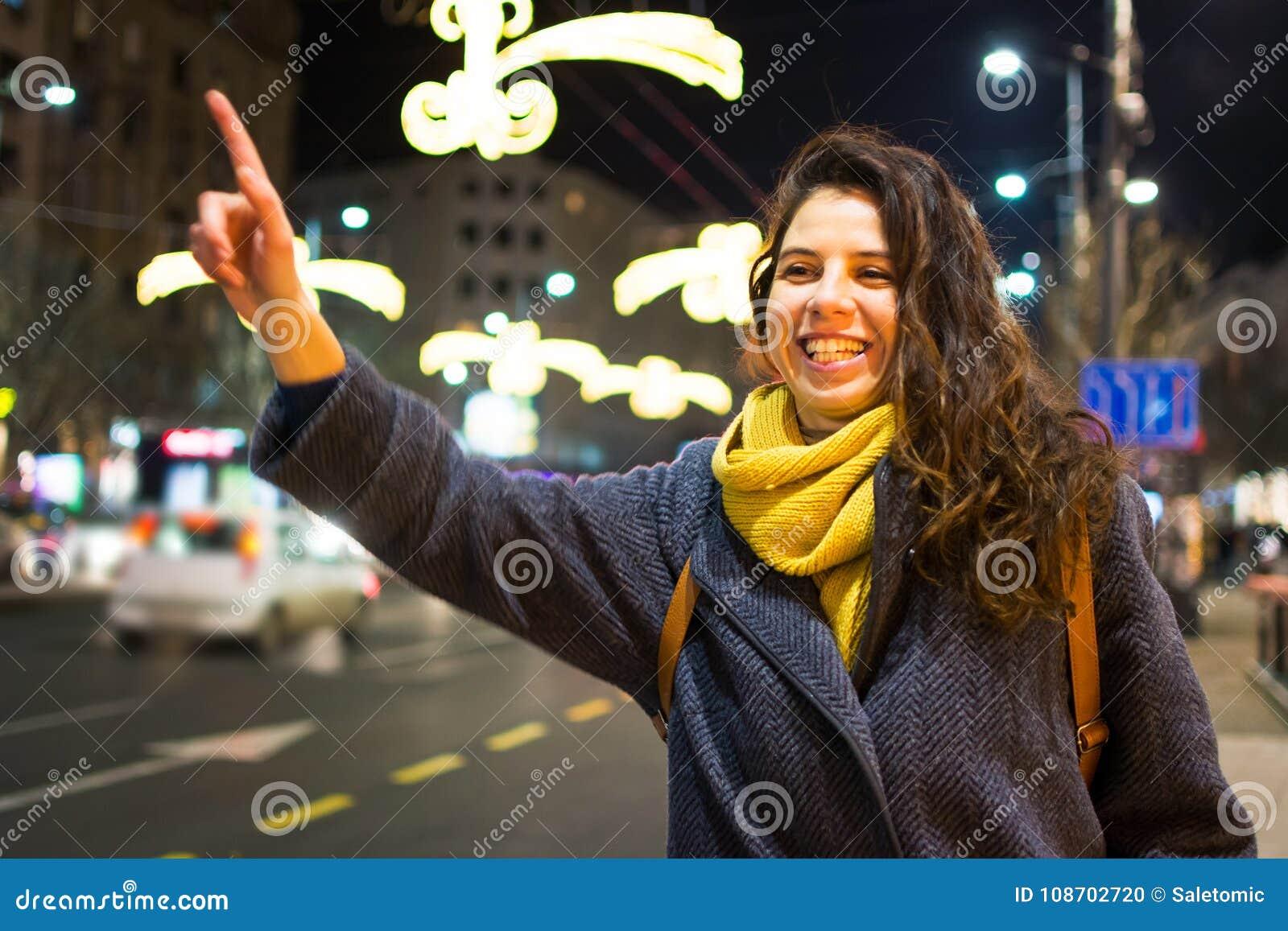 Girl calling taxi in urban environment