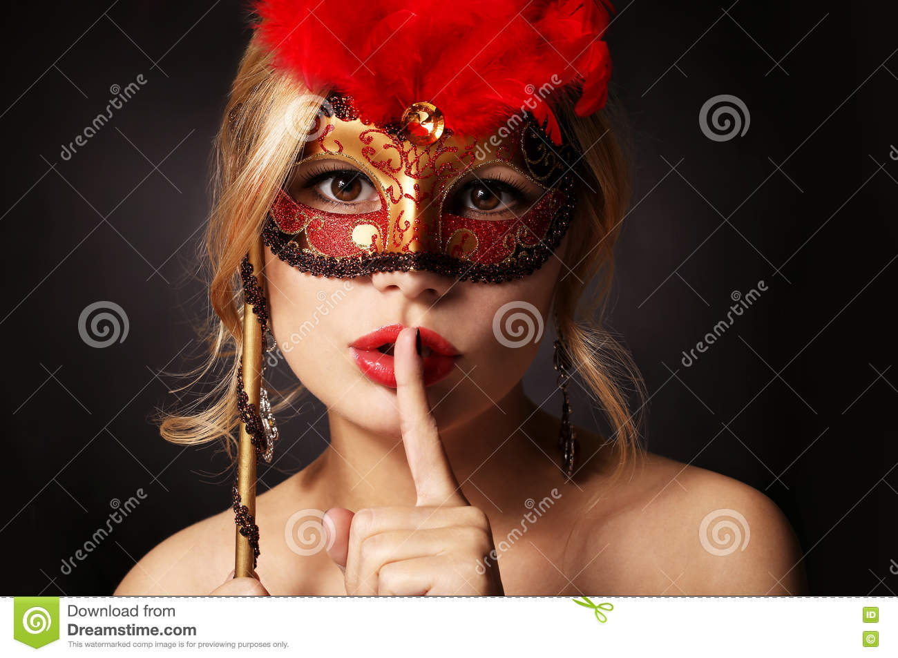 Girl with carnival mask. woman with finger on her red lips showing hush