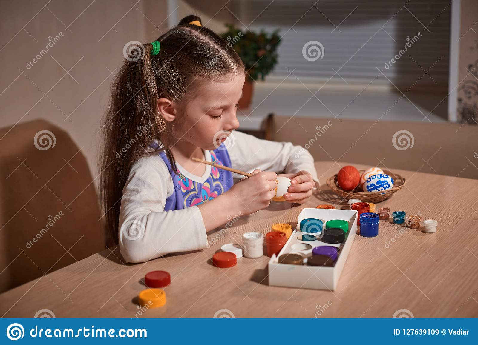 Girl Caucasian appearance with two pigtails sitting at a large wooden table and paints a brush and eggs for Easter