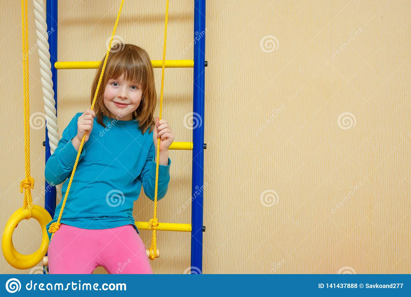 The girl cheerfully sits on a sports ladder