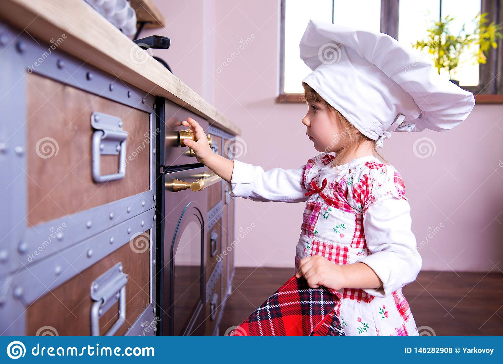 Girl in chef`s hat is putting gingerbread cookies in the oven