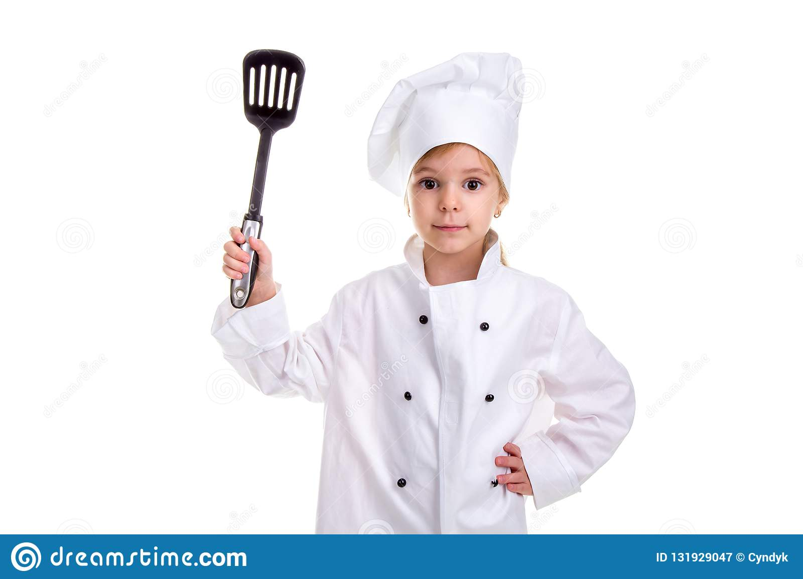 Girl chef white uniform isolated on white background. Holding black scapula up with another hand on the waist. Looking