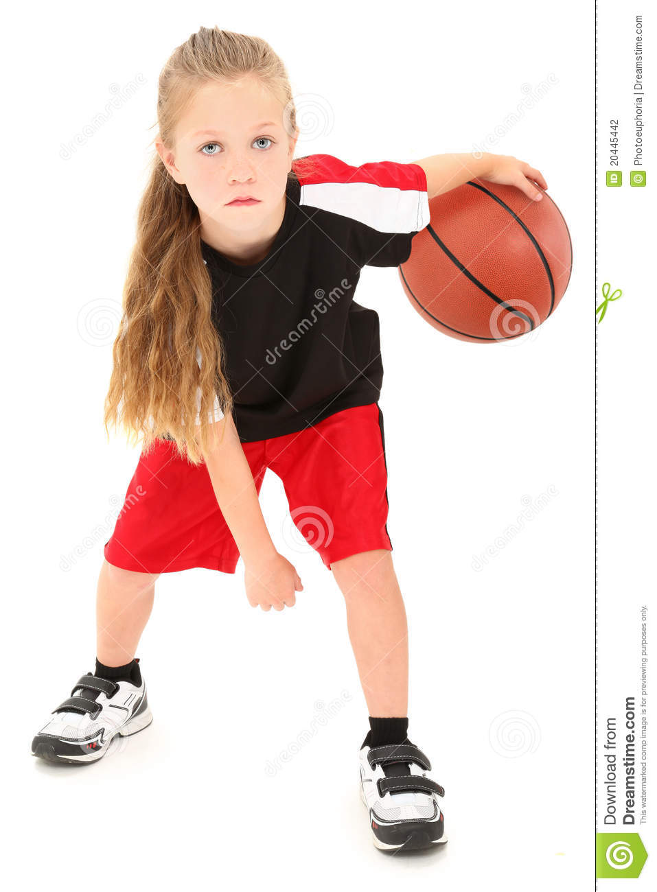 Serious girl child basketball player in uniform dribbling ball between ...