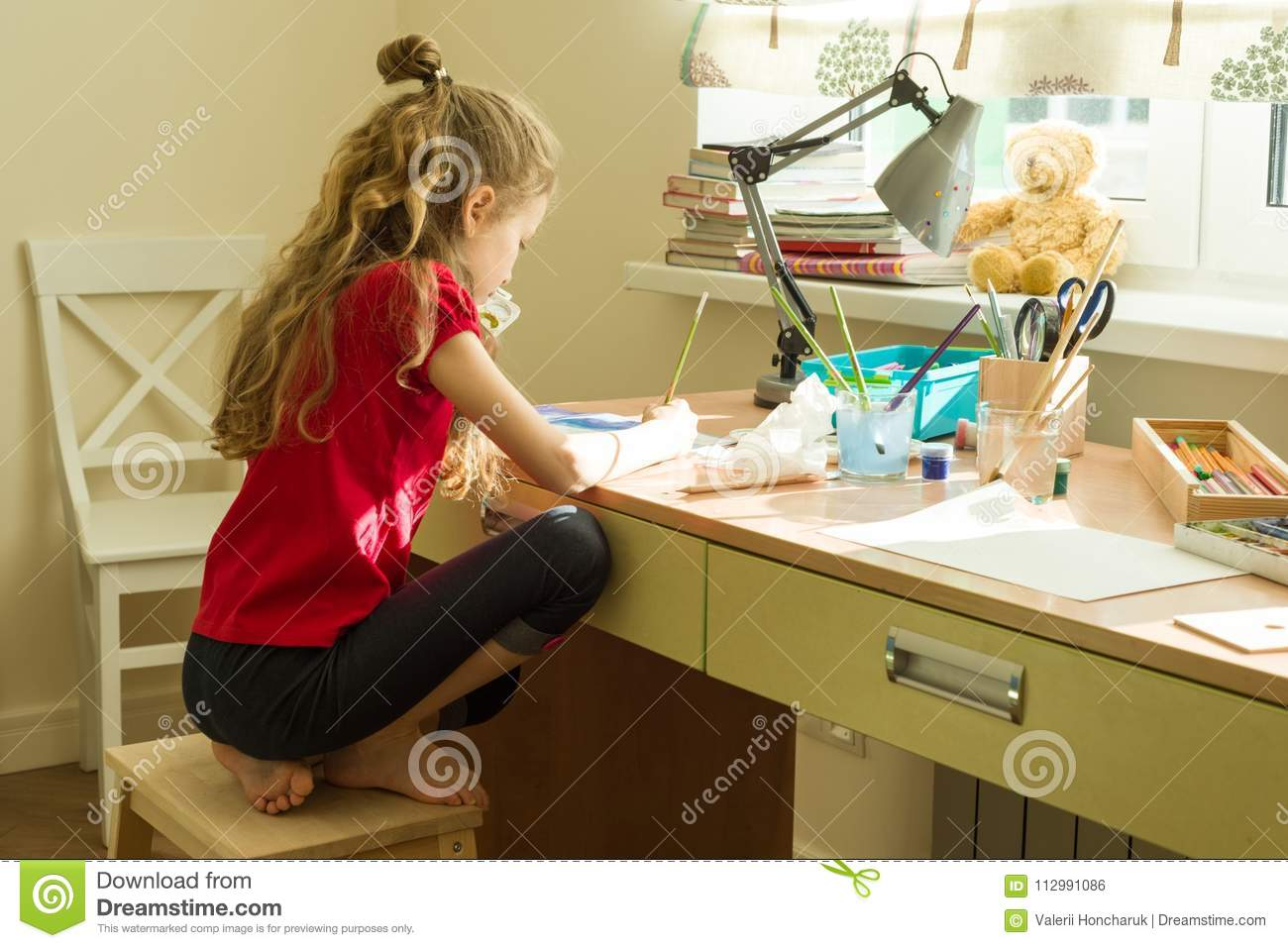 Girl child draws watercolor at the table at home. Child creativity, recreation, development.
