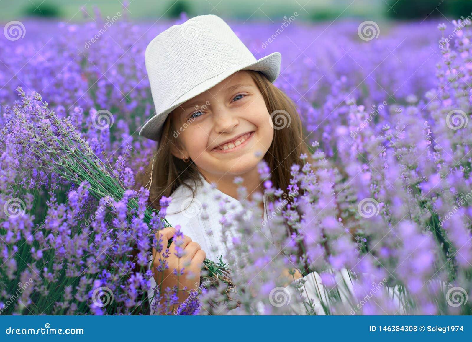 Girl child is in the lavender flower field, beautiful summer landscape