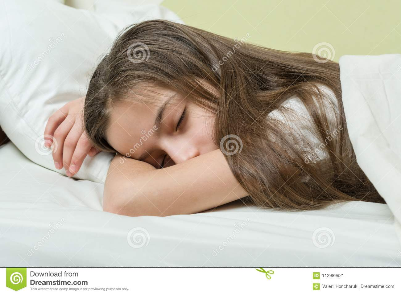 Girl child with long brown hair sleeping on a pillow in bed