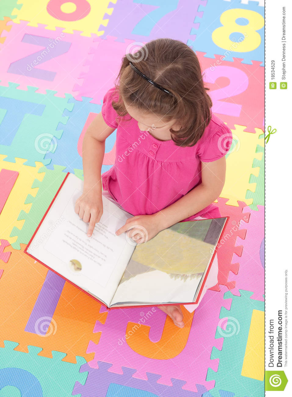 Girl Child Reading Kids Book On Alphabet Mat Stock
