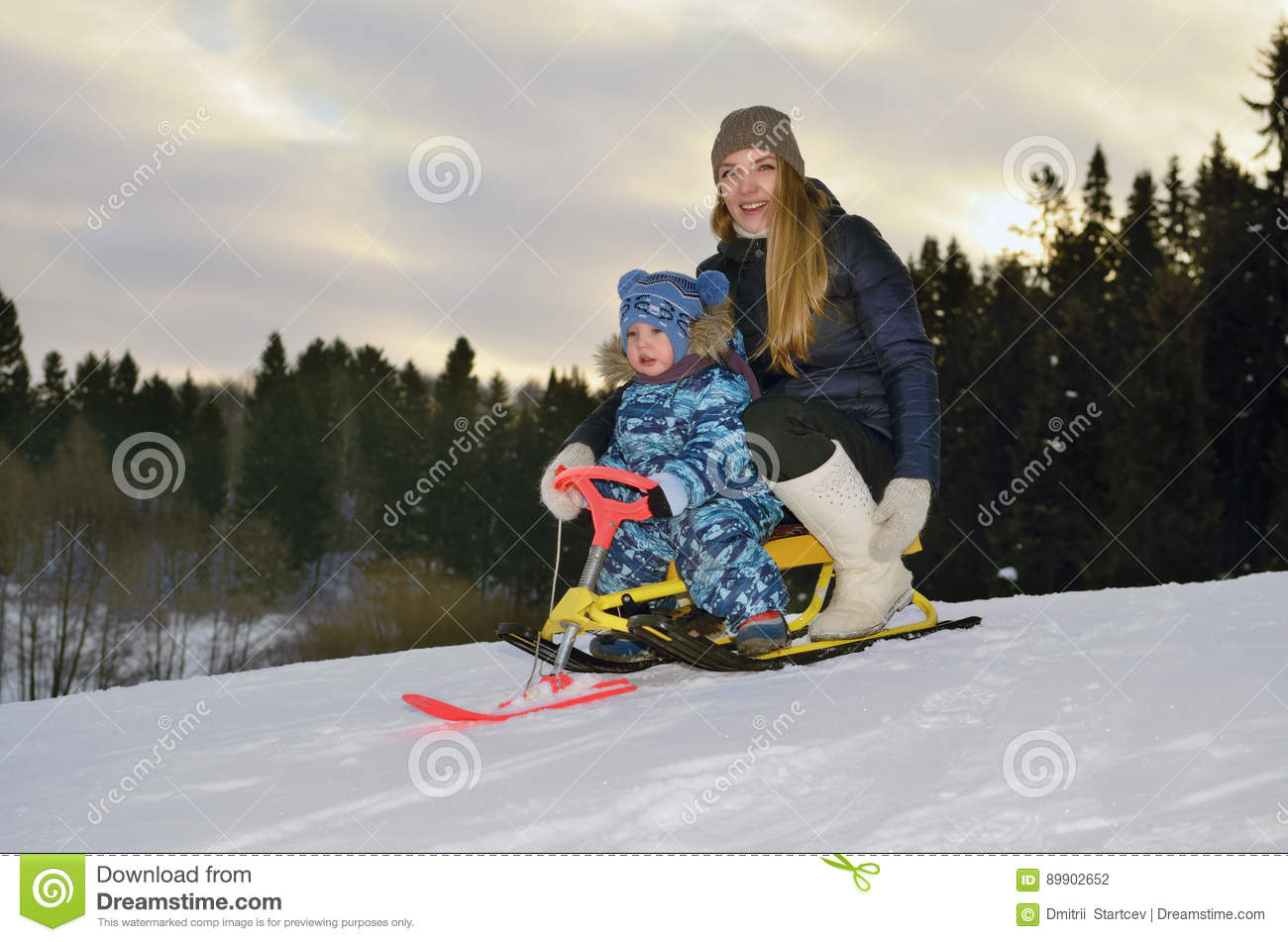 A girl with a child riding on a sledge