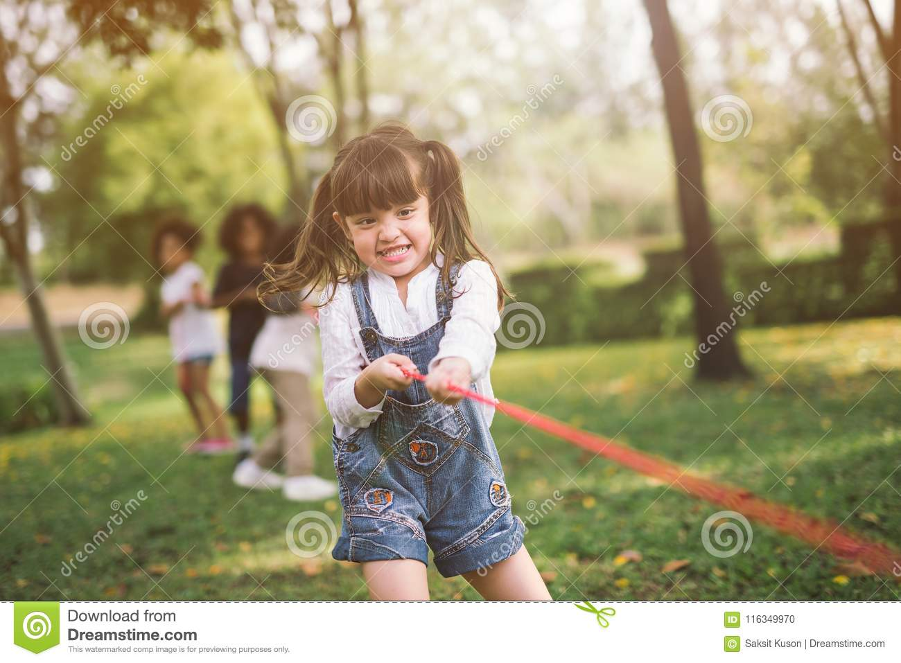 Girl children playing tug of war at the park.