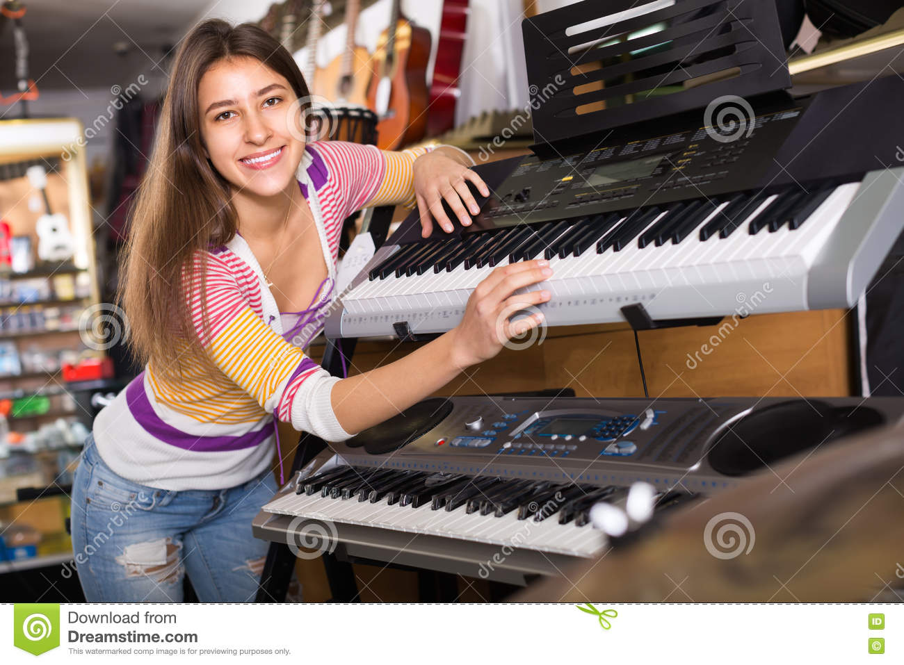 Girl Choosing Synthesizer In Store Stock Photo - Image of