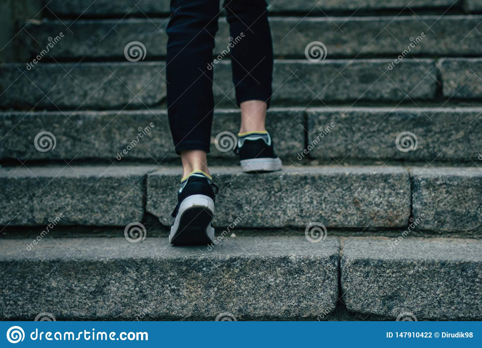 The girl climbs on concrete stairs