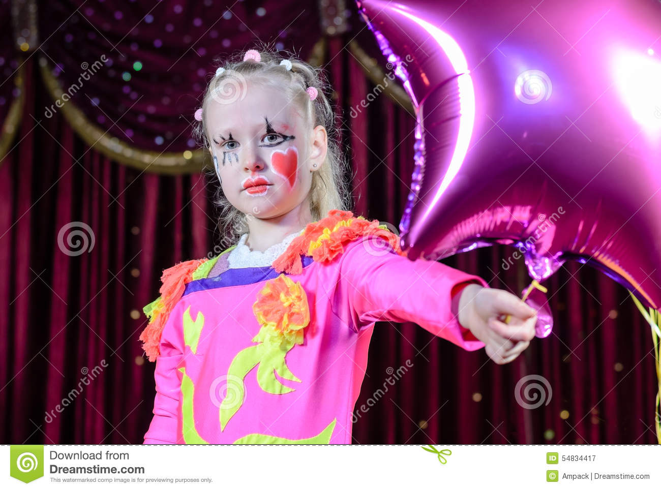 Costume holding star shaped balloon on stage in front of red curtain