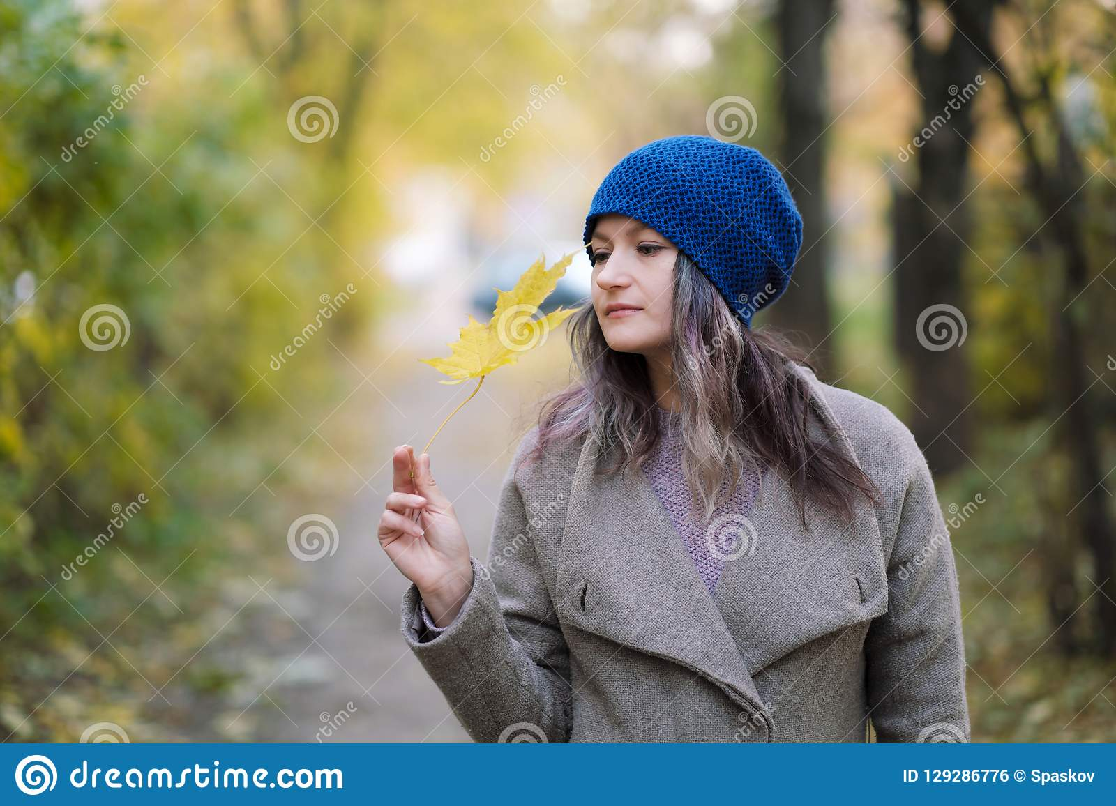 The girl in a coat and blue hat on a background of autumn trees and maple leaves.
