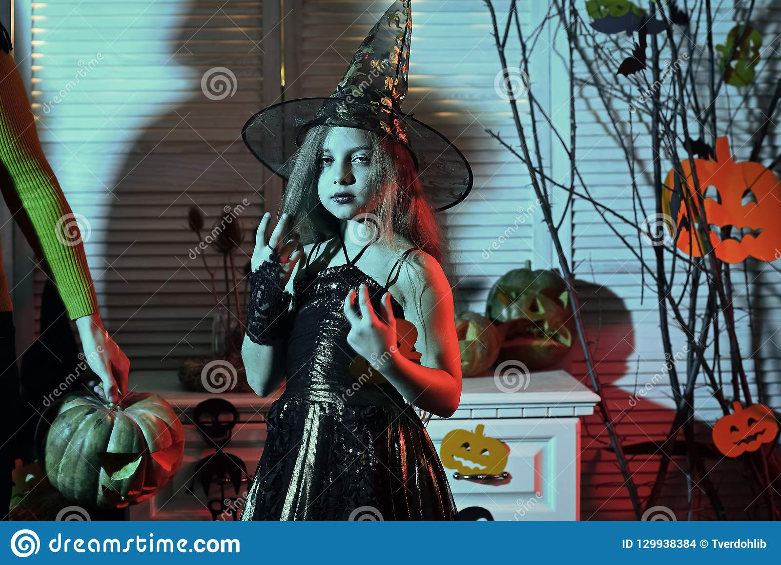 Girl with confident face on blue spooky carnival room background.