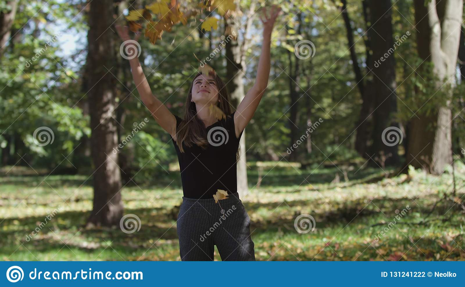 Girl is covering her face and waving a maple tree branch with yellow leaves in autumn park. Slow motion