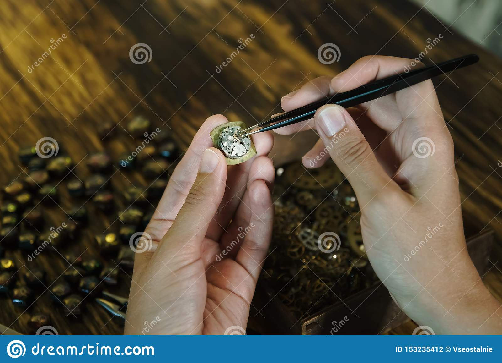 Girl craftsman dismantles watches at workspace