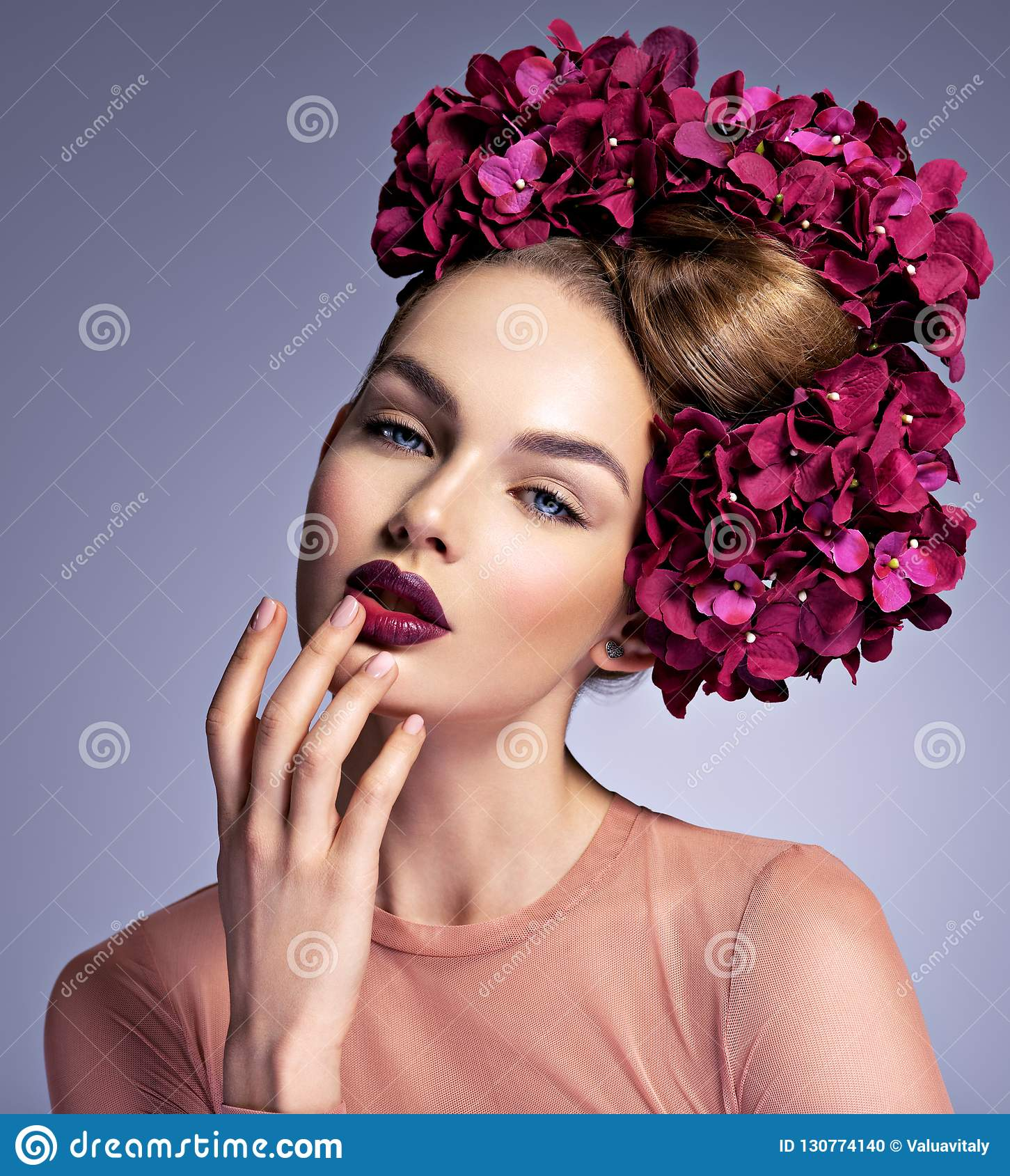 Girl with a creative hairstyle and blossoming flowers.