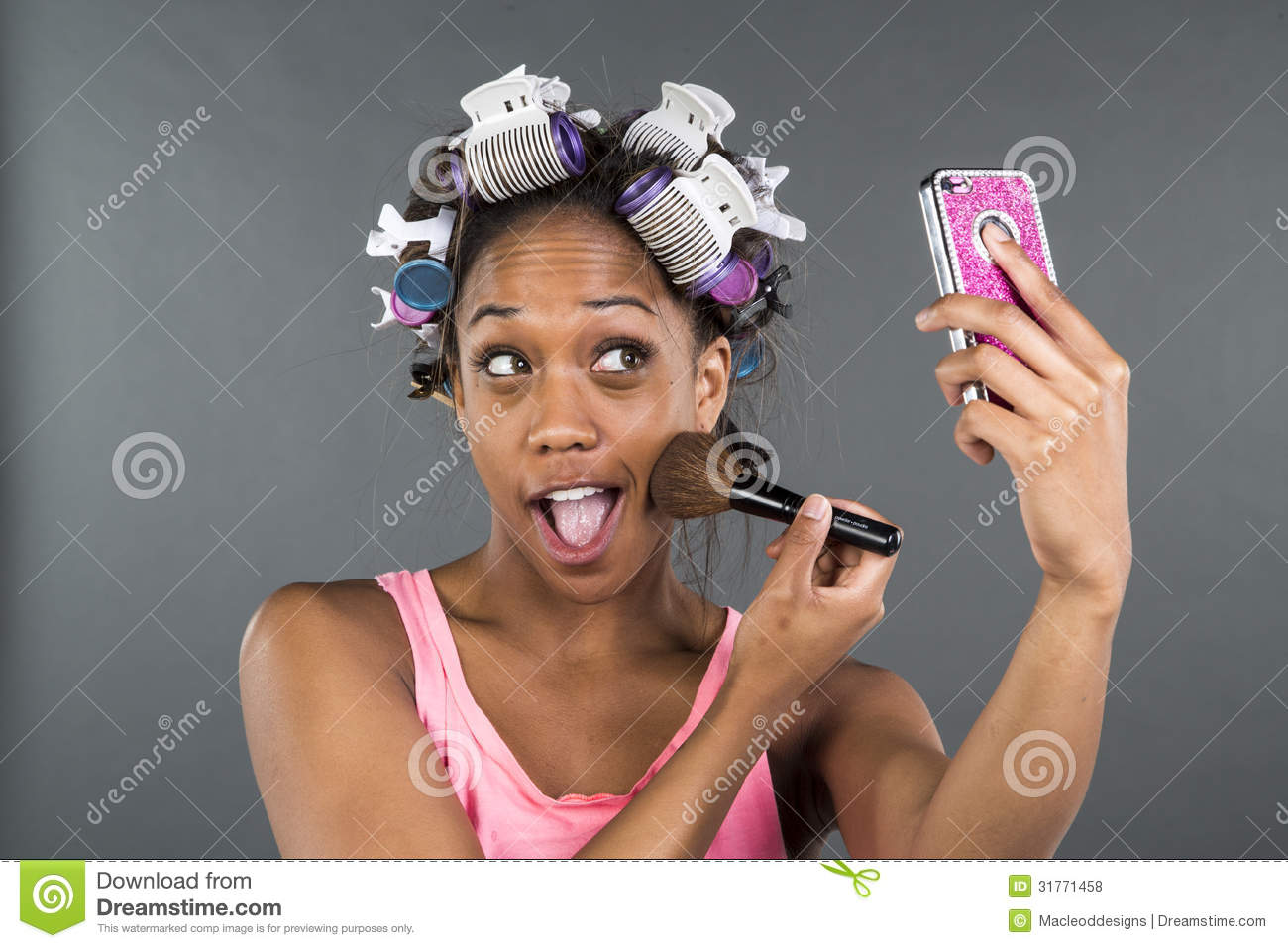 A Girl With Curlers In Her Hair Looking At Phone Royalty
