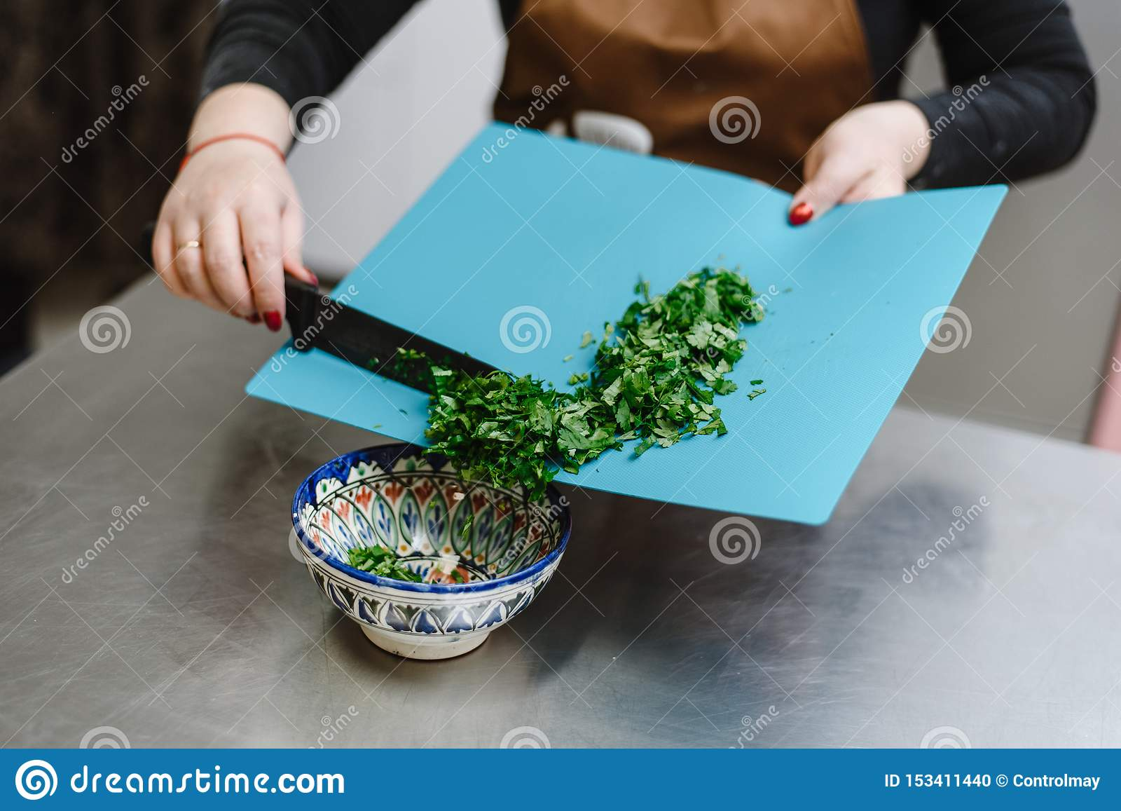 The girl cuts greens, onions, parsley and various seasonings with a knife on a cutting board. Woman cook cuts salad for cooking.