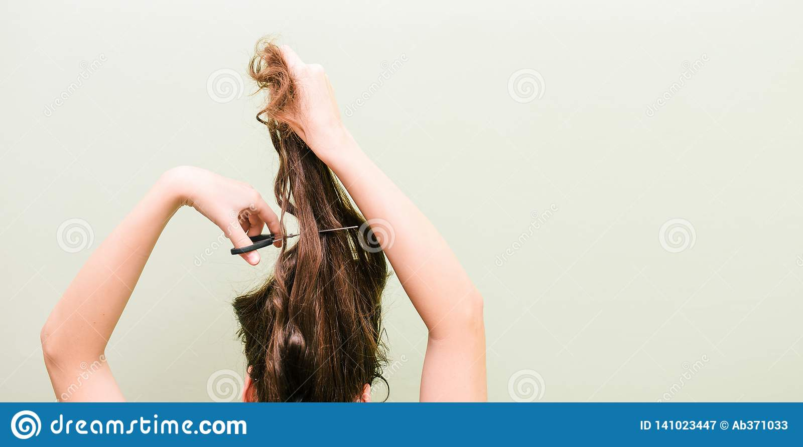 The girl cuts her hair with scissors. The concept of fashion and care. Woman cuts her long hair
